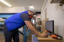 Vista lateral del hombre caucásico concentrado con orejeras alrededor del cuello trabajando en la computadora en el taller - foto de stock