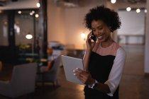 Вид спереди на красивую молодую деловую женщину смешанной расы, разговаривающую по мобильному телефону, глядя на цифровой планшет в офисе — стоковое фото