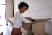 Portrait of happy Mixed-race businesswoman unpacking cardboard box in modern office. She is looking and smiling at camera — Stock Photo