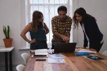 Разнообразные деловые люди обсуждают за ноутбуком за столом в офисе — стоковое фото