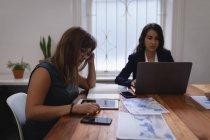 Vue latérale de Diverses femmes d'affaires travaillant sur ordinateur portable et tablette numérique à la table au bureau — Photo de stock