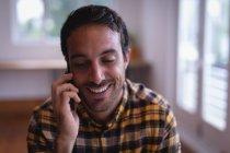 Vue de face d'un heureux exécutif masculin caucasien parlant sur un téléphone portable dans le bureau — Photo de stock