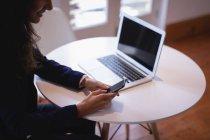 Vista lateral de una mujer de negocios de raza mixta de cabello castaño usando un teléfono móvil mientras trabaja en una computadora portátil en la oficina - foto de stock