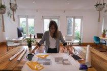 Vue de face de belle femme d'affaires caucasienne regardant le plan dans le bureau — Photo de stock