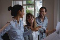 Vista lateral do sorriso Diversas pessoas de negócios discutindo sobre o projeto no escritório — Fotografia de Stock
