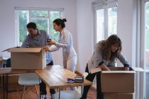 Side view of Diverse business people packing cardboard boxes in the office — Stock Photo