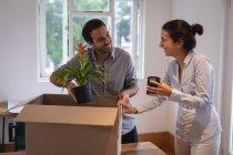 Vorderansicht eines kaukasischen Geschäftsmannes und einer Geschäftsfrau mit gemischter Rasse, die miteinander interagieren, während sie im Büro Kartons packen — Stockfoto