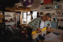 Seitenansicht eines aufmerksamen kaukasischen Zimmermanns, der während seiner Arbeit in der Werkstatt eine Holzplanke misst — Stockfoto