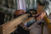 Mid section of carpenter using clamp on wooden plank in workshop — Stock Photo