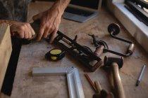 Средняя часть плотника держит гладкую плоскость в мастерской — стоковое фото