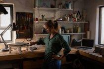 Боковий вид уважного кавказької жіночої тесляра розпис табурет в майстерні — стокове фото