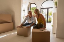 Front view of happy mature Caucasian couple looking at each other and relaxing after moving into their new house — Stock Photo