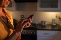 Metà sezione di donna caucasica matura sorridente e utilizzando il telefono cellulare in cucina a casa all'alba — Foto stock