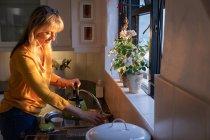 Vue latérale de femme blanche mature remplissant la bouilloire avec de l'eau dans l'évier dans la cuisine à la maison au lever du soleil — Photo de stock