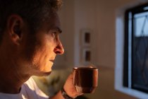 Side view of thoughtful mature Caucasian man having coffee and looking through the window in kitchen at home on sunrise — Stock Photo