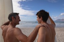 Vue arrière du père et du fils caucasiens avec planche de surf interagissent les uns avec les autres à la plage — Photo de stock
