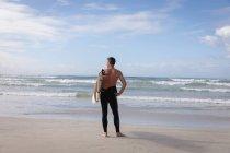 Вид сзади на кавказца, стоящего с доской для серфинга на пляже в солнечный день — стоковое фото