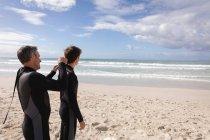 Задний вид на Кавказского отца помогает сыну носить мокрый костюм на пляже в солнечный день — стоковое фото