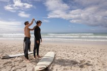 Side view of Caucasian father assist son to wear wetsuit at beach on a sunny day — Stock Photo