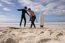 Низький кут зору Кавказького батька допомогти синові їздити на серфінгу на пляжі в сонячний день — стокове фото