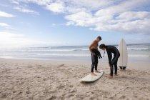 Вид спереди кавказского отца помогает сыну кататься на доске для серфинга на пляже в солнечный день — стоковое фото