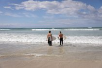 Rear view of Caucasian father and son with surfboard standing in sea — Stock Photo