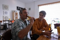 Side view of Caucasian father and son drinking beer at home — Stock Photo