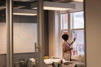 Distant d'une femme d'affaires afro-américaine écrivant sur un tableau dans la salle de conférence au bureau — Photo de stock