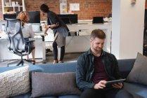 Высокий угол обзора улыбающегося кавказского бизнесмена с помощью цифрового планшета на диване в офисе — стоковое фото