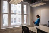 Seitenansicht einer kaukasischen Geschäftsfrau mit digitalem Tisch im Konferenzraum im Büro — Stockfoto