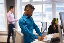 Vista laterale dell'uomo d'affari afro-americano che guarda fotografie e colleghi Diversi che lavorano in background in ufficio — Foto stock
