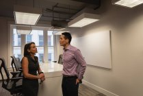 Vista lateral de diversos empresários discutindo uns com os outros na sala de conferências no escritório — Fotografia de Stock