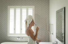 Vista laterale della bella donna pensierosa in piedi davanti allo specchio mentre tiene lo spazzolino da denti — Foto stock