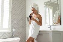 Bella donna che usa il suo telefono mentre si lava i denti in bagno — Foto stock