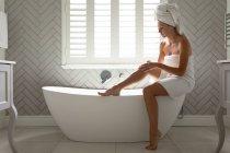 Красивая женщина массирует ноги на ванне в ванной комнате дома — стоковое фото