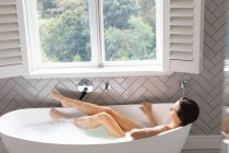 Woman relaxing in the bathtub in bathroom at home — Stock Photo
