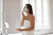 Вид збоку жінки нанесення маски для обличчя у ванній після лазні — стокове фото