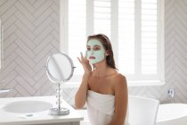 Жінка дивиться у дзеркало і застосовує маску обличчя після ванни у ванній кімнаті. — стокове фото