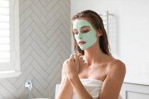 Крупний план вдумливого жінку з маскою обличчя сидить у ванній — стокове фото