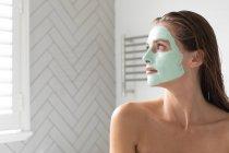 Primer plano de mujer pensativa con máscara facial mirando por la ventana en el baño - foto de stock