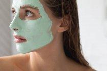 Close-up de mulher com máscara facial no banheiro — Fotografia de Stock
