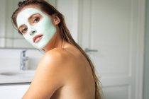 Крупним планом красива жінка в обличчя маска дивлячись на камеру — стокове фото