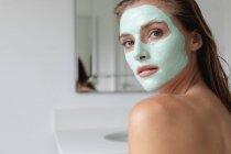 Крупним планом жінка в обличчя маска дивлячись на камеру у ванній — стокове фото