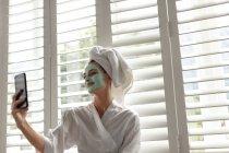 Femme souriante en peignoir prenant un selfie à la maison — Photo de stock