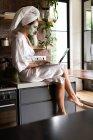 Donna in accappatoio seduto sul bancone della cucina e utilizzando il computer portatile al mattino — Foto stock