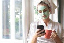 Bella donna in maschera facciale utilizzando il telefono cellulare vicino alla finestra a casa — Foto stock
