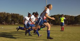 Side view of diverse women soccer players running at sports field on a sunny day — стоковое фото
