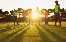 Low angle view of diverse female soccer players standing together at sports field at dusk — Stock Photo