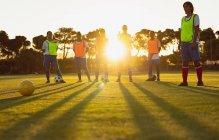 Низкий угол обзора различных женщин-футболистов, стоящих вместе на спортивной площадке в сумерках — стоковое фото