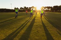 Rear view of diverse female soccer players playing at sports field at dusk — Stock Photo